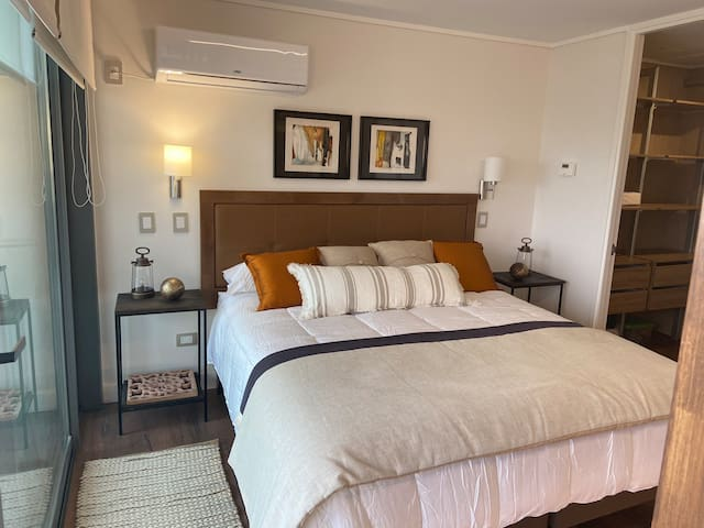 Habitación equipada con cama King, queda con sábanas blancas.
