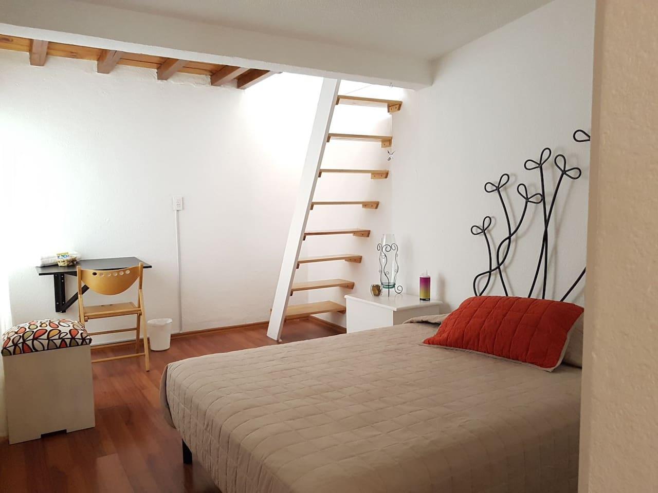 Habitación con cama matrimonial y pequeño tapanco