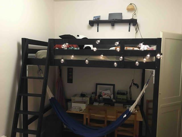 Première chambre avec carrelage et lit double en mezzanine, coin bureau et possibilité de se relaxer dans un hamac
