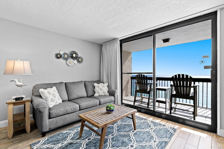 couch and coffee table with view of balcony overlooking the beach