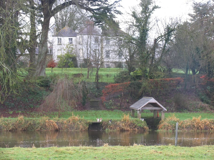 View from river showing boat house and main house and loft in background