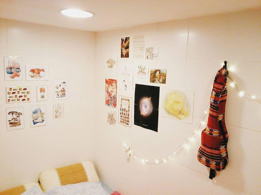 Cantinho da cama com tomada, luzinha de natal de cabeceira e muita arte na parede.