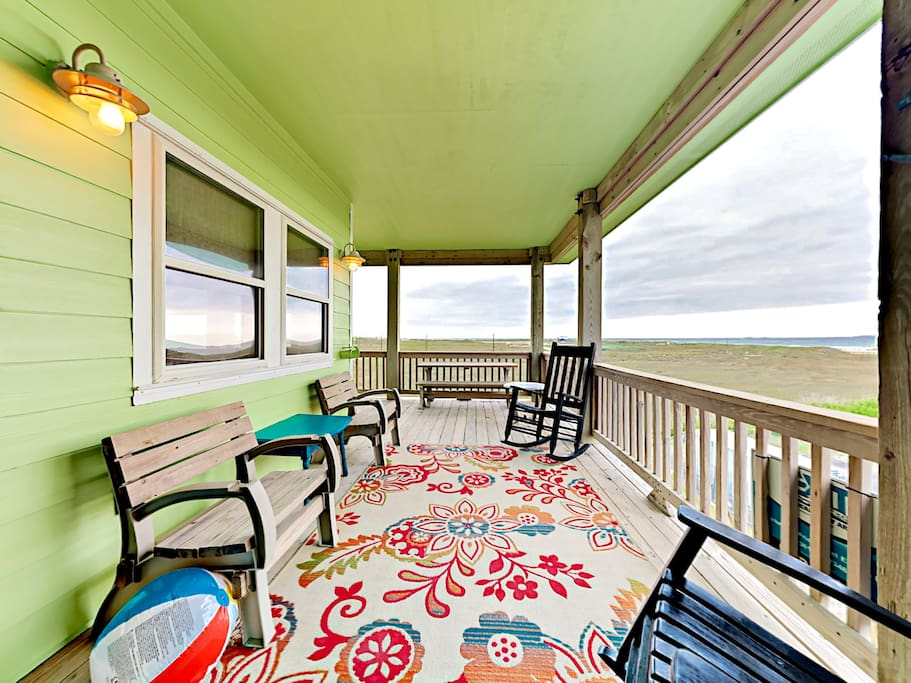 Enjoy the Gulf view from a wraparound deck from colorful chairs