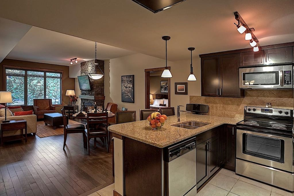 The sleek kitchen features stainless steel appliances and a breakfast bar.