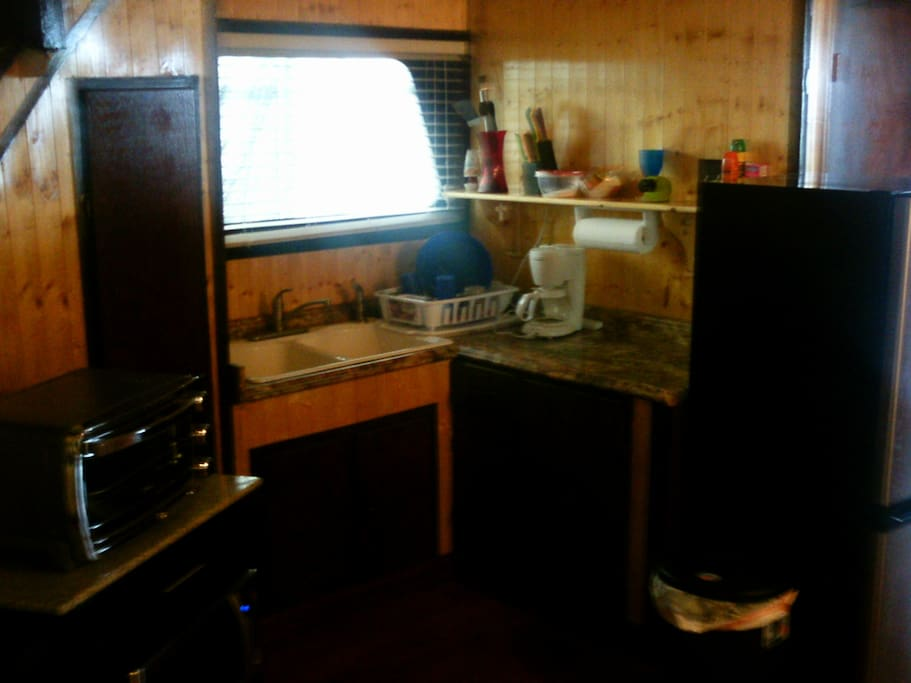 Kitchen area equipped with microwave, coffee pot, toaster oven, and refrigerator