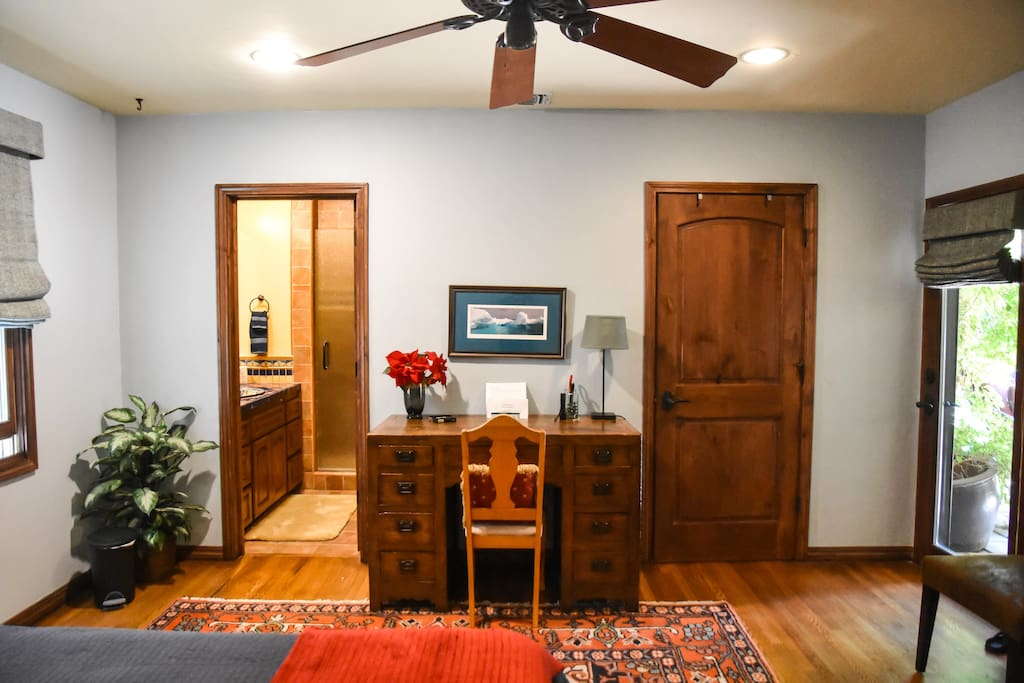 Doors to private bath with shower on left and to walk-in closet on the right of desk.