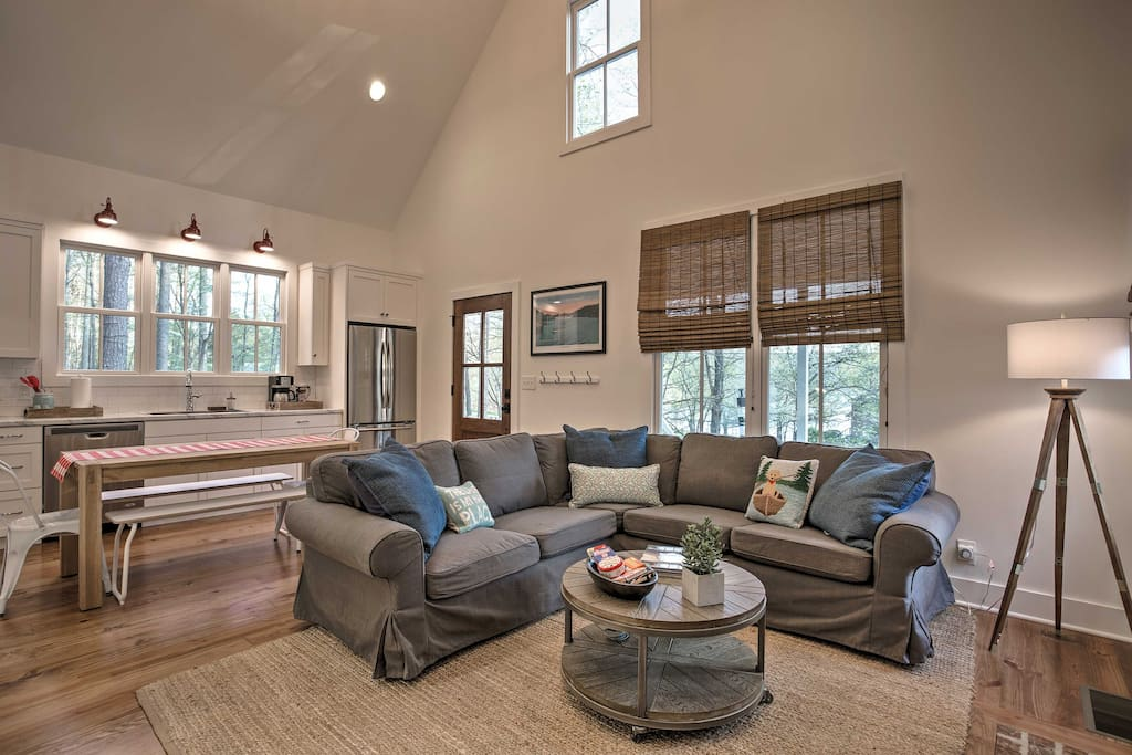 Step into the open-concept living area where you'll find a sectional sofa facing a beautiful brick fireplace.