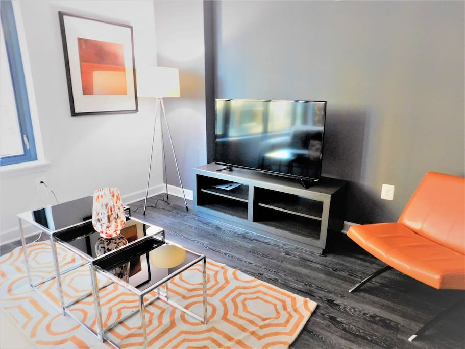 Pops of orange liven up the space. Oh, and that Smart TV you see helps.