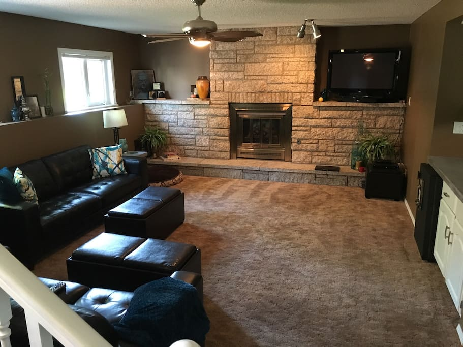 Guest living room / den area with satellite tv and Apple TV. Also has mini wet bar and private mini fridge. Flows down from shared kitchen. 1 queen bedroom and full bathroom.