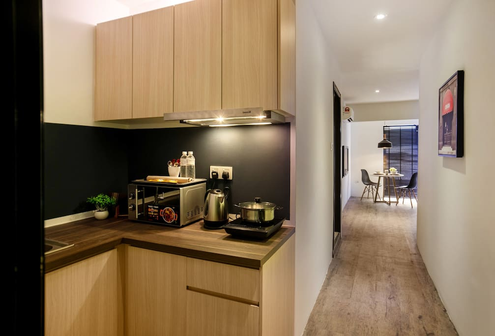 Full kitchen amenities with microwave oven, induction cooker, kitchen hood, pots and pans.