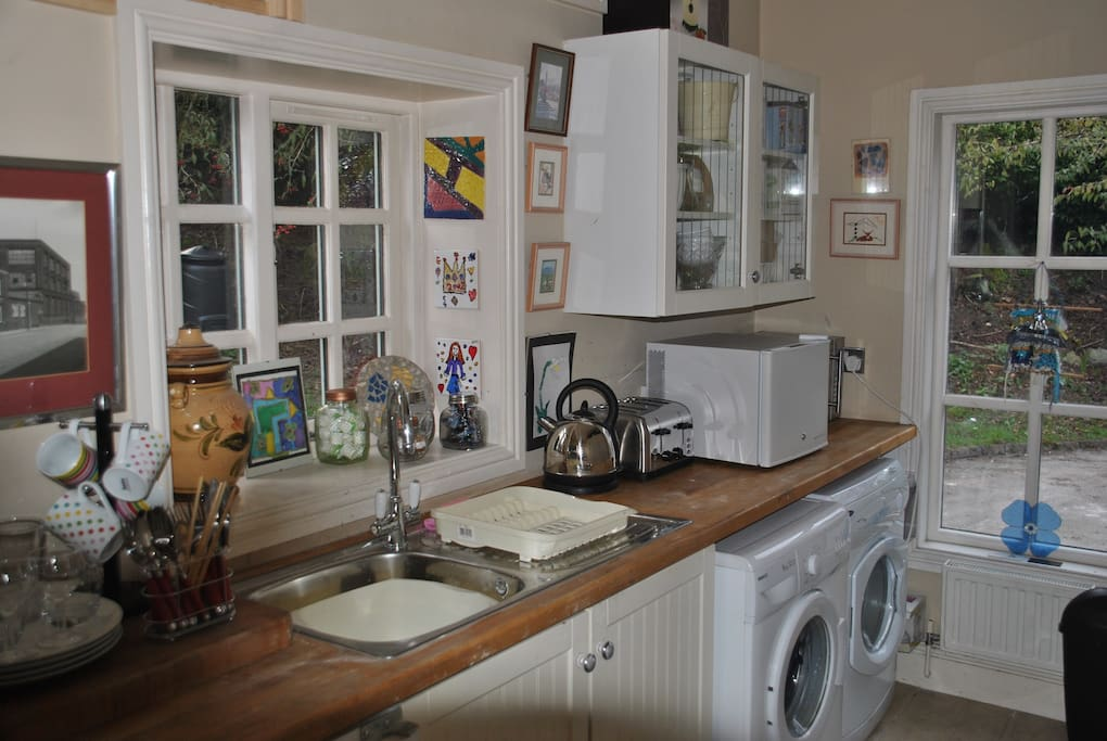 A utility room has a microwave, small fridge, cutlery, crockery and kettle for your use.
