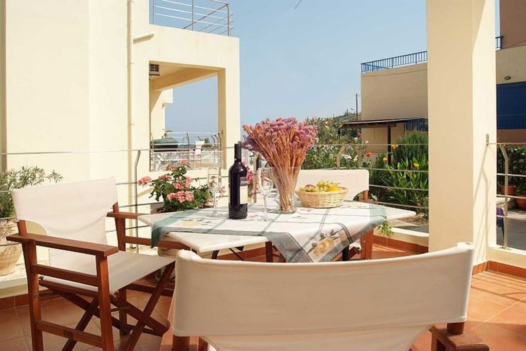 The spacious balcony with patio furniture and barbecue.