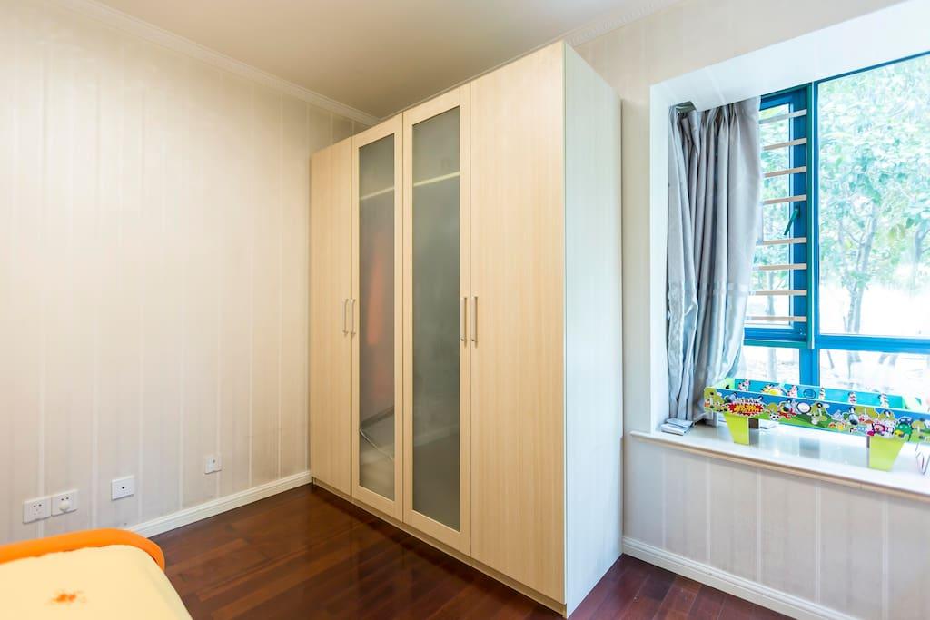 四扇门大衣橱,提供了足够的容纳空间,遮光窗帘保证充足睡眠,窗外是桂花树。