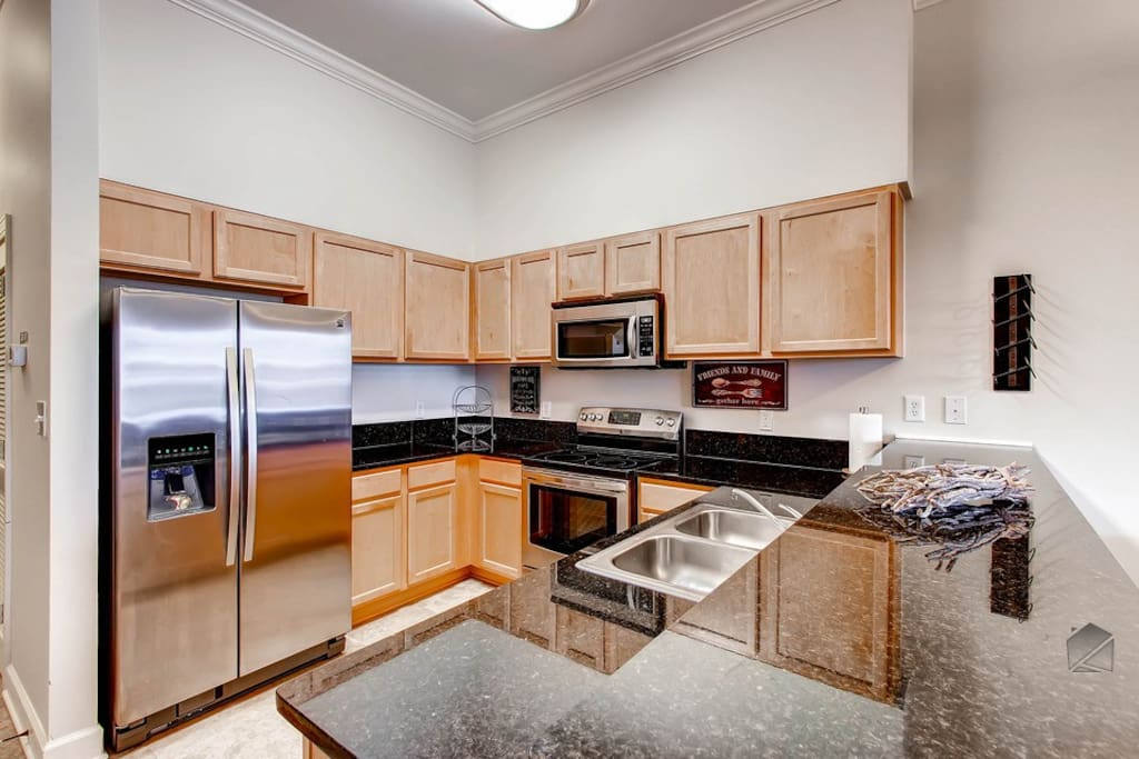 This modern kitchen has granite countertops and everything you'll need to cook a great meal which features a stainless steel refrigerator and ice dispenser.