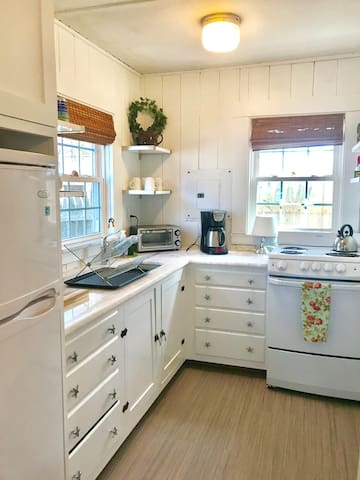 Newly renovated kitchen with Marble counters, new stove & fridge. Stocked with pots & pans, dinnerware & spices.