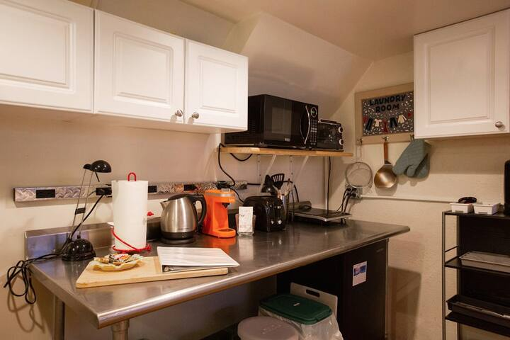 Sleek stainless  steel table hosts kitchenette equipment: a hot pot, a Keurig coffee maker, a hot plate, and a toaster.  Above there is a microwave and toaster oven.