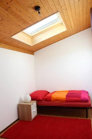 Camera da letto rossa con lucernario