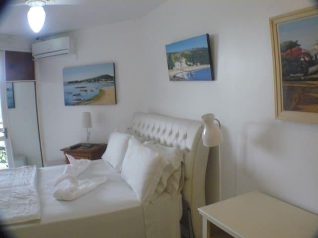 Vista do quarto de dormir do apto Deluxe de 49m2 com ar Split e TV