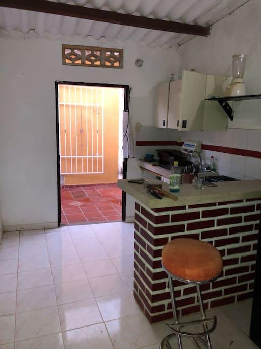 cocina tiene licuadora, estufa con horno, gabinetes, purificador de agua, platos, vasos, cubiertos.