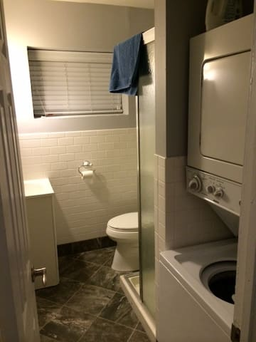 Upstairs bathroom with stall shower and laundry.