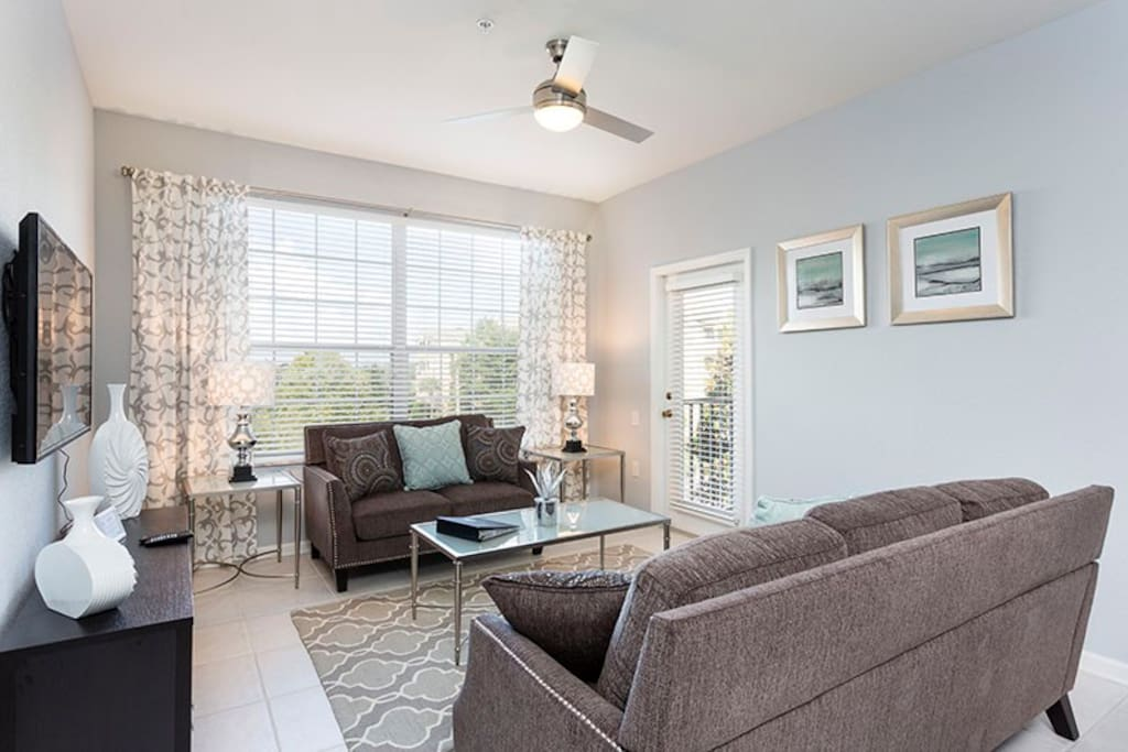 The living room features a ceiling fan, flatscreen cable TV and walkout balcony