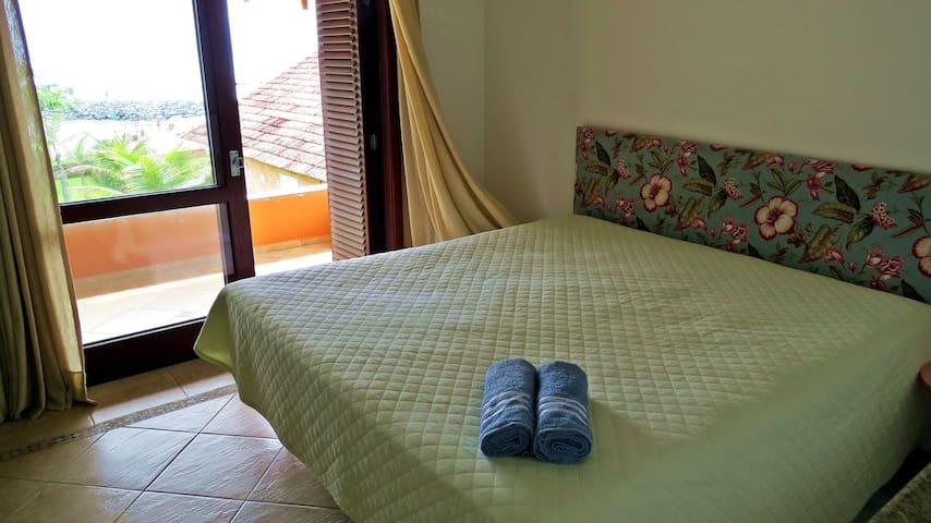 Quarto com cama de casal King Size e sacada com vista para o mar.
