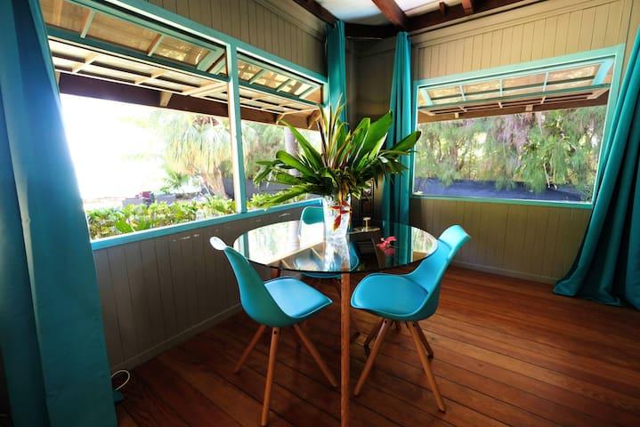 le coin repas à l'intérieur , avec vue sur le jardin et le lagon .