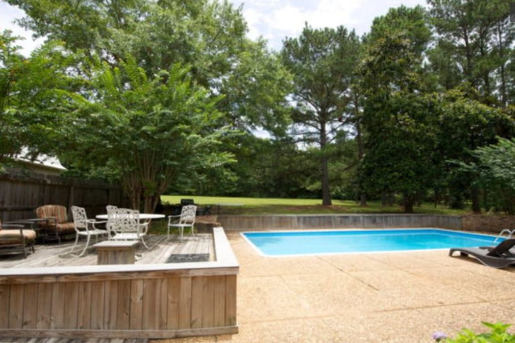 Walk out of the master suite to the pool and wooded backyard