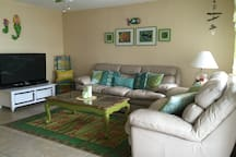 The living room has lots of comfortable seating, a ceiling fan, and a large flat screen tv