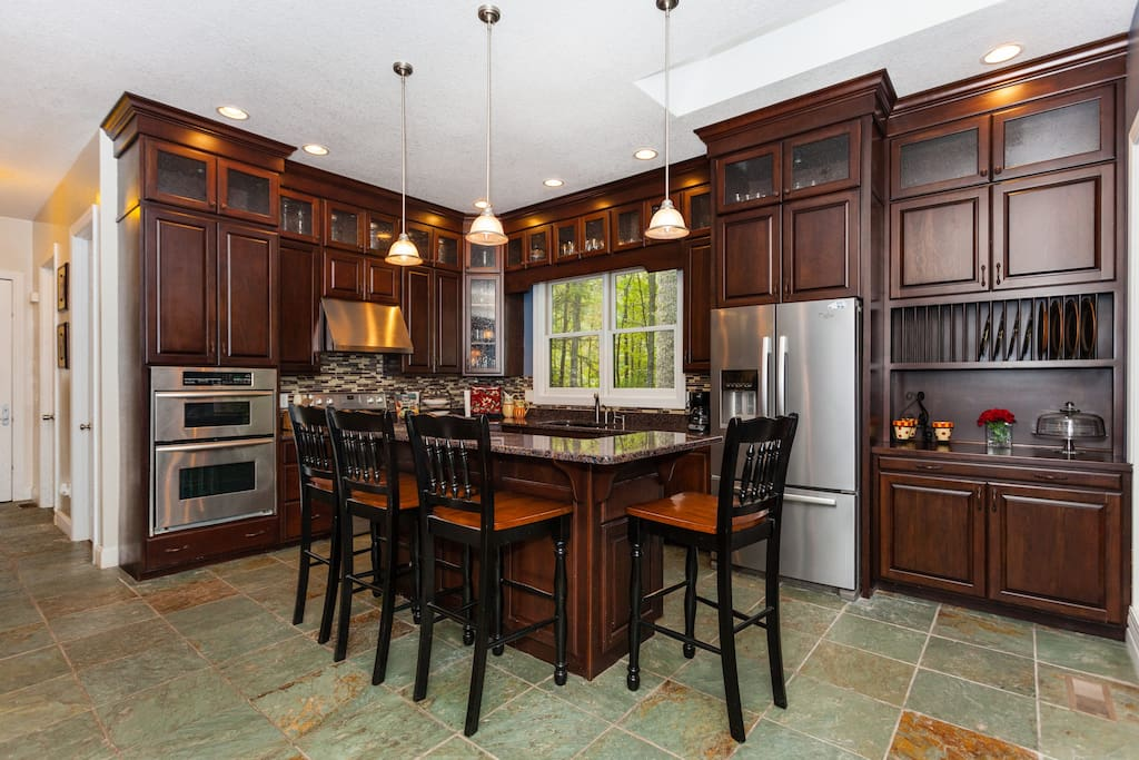 Beautiful kitchen with floor to ceiling cabinets granite countertops and dual ovens.
