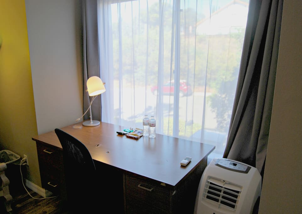 Full Size Desk with lots of morning light.  Black out curtains are also supplied with an small portable air conditioner.