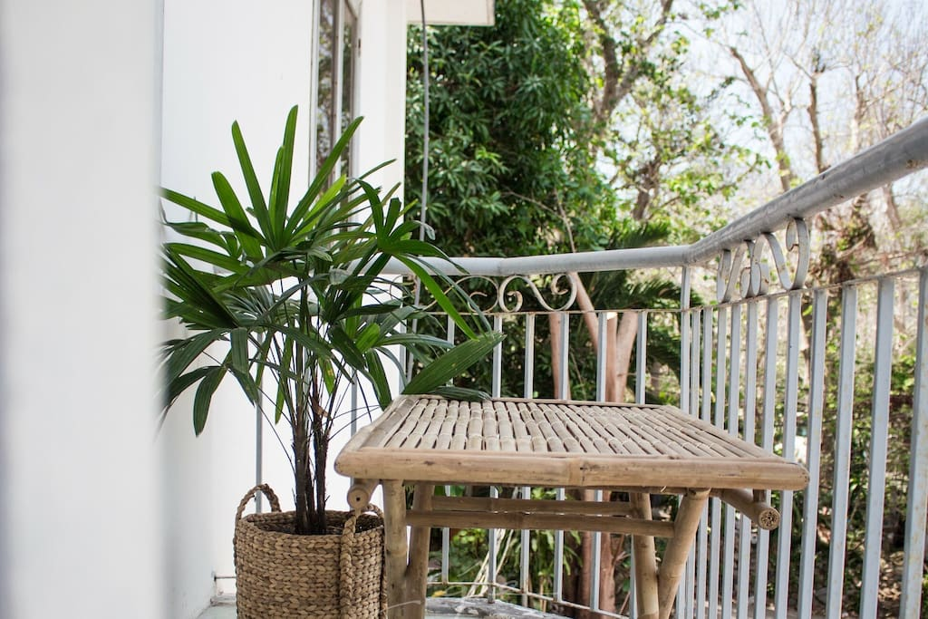A mini bamboo table with plants in the balcony, which is suitable for a morning coffee or simply enjoy the fresh air in the early morning.