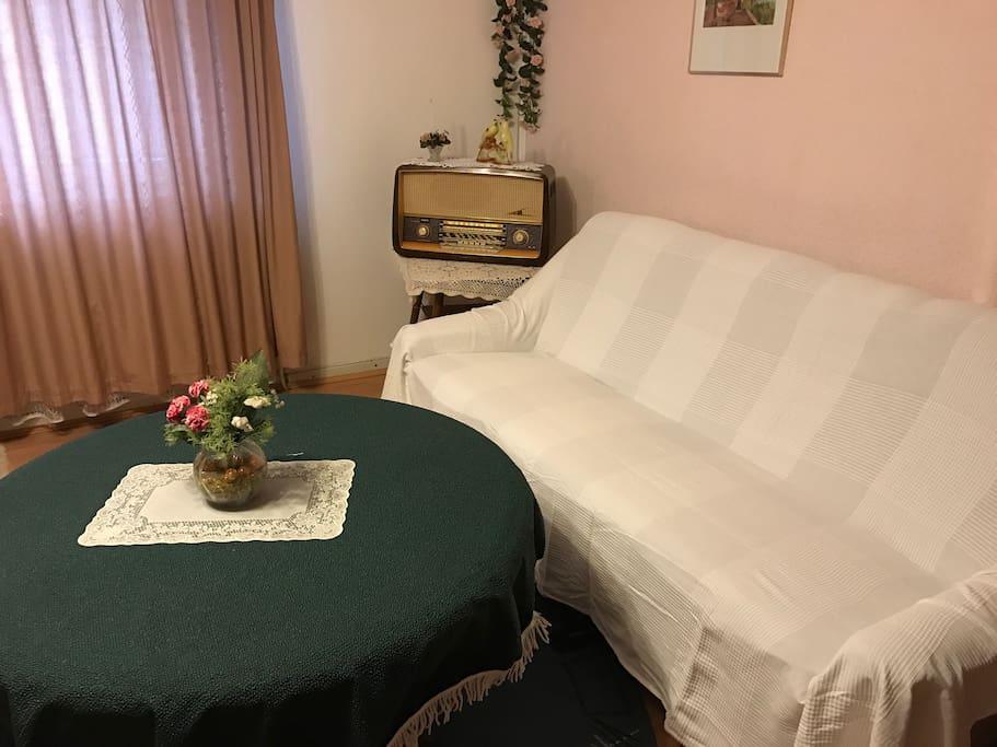 Zimmer mit TV, Bett, Sitzgelegenheit und Schrank