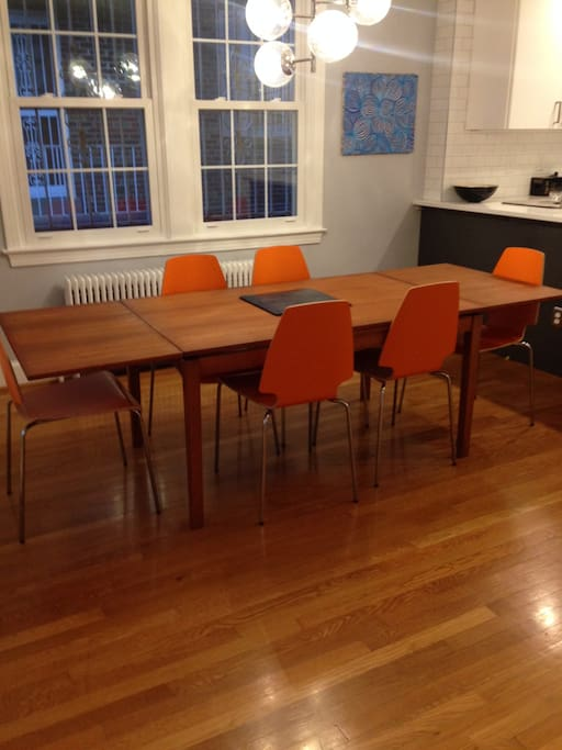 Large dining table facing open kitchen.
