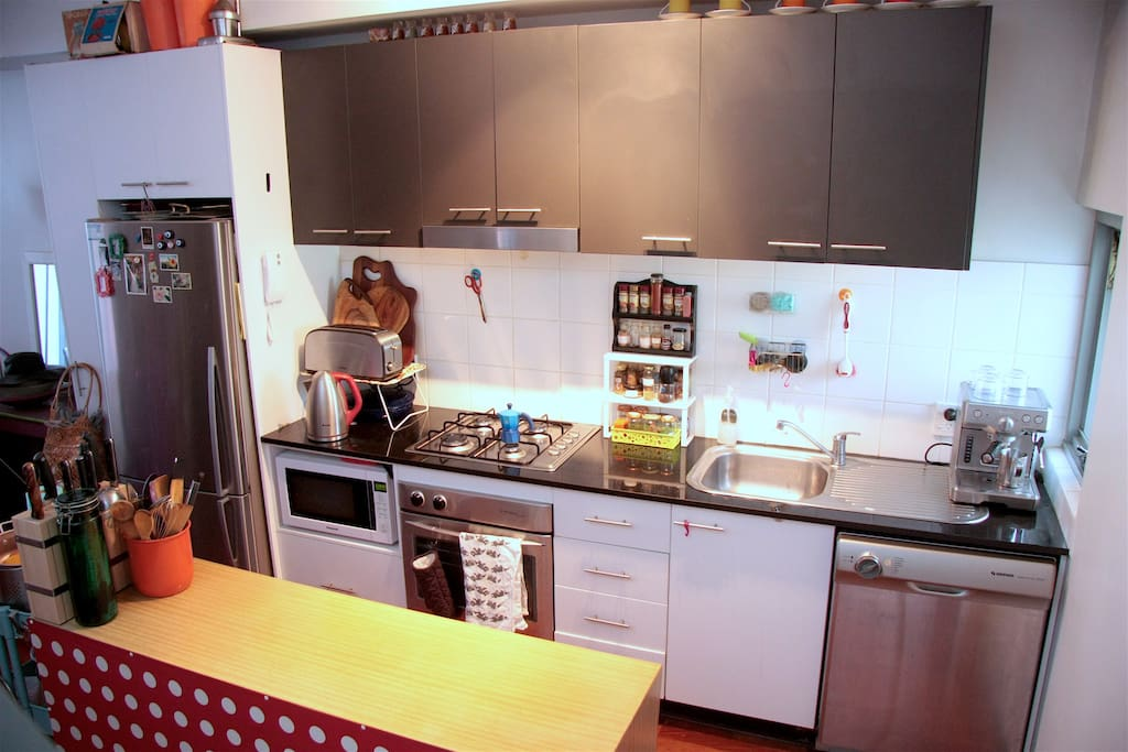 A fully equipped kitchen with stove, oven, microwave, dishwasher and well stocked spice rack