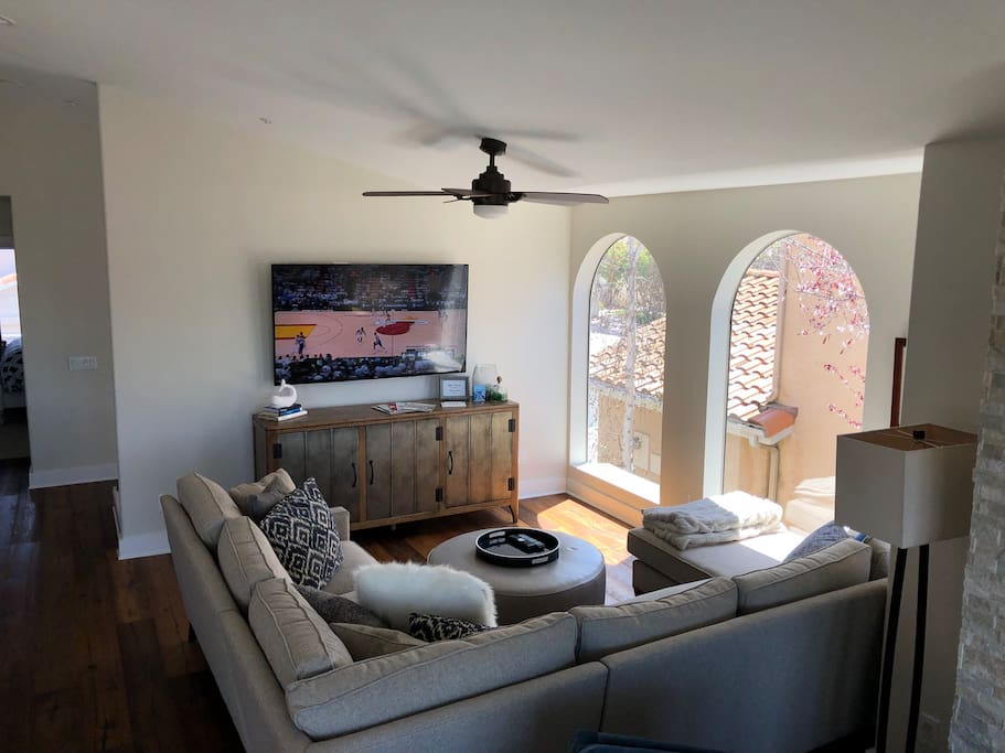 Living room space with great natural light, an L shaped couch, and TV