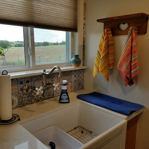 The view! Lovely! Farm sink, Spanish porcelain tile backsplash, small fridge, instant hot water and the view!!