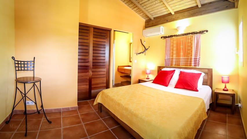La chambre jaune avec climatisation et salle de bains privative