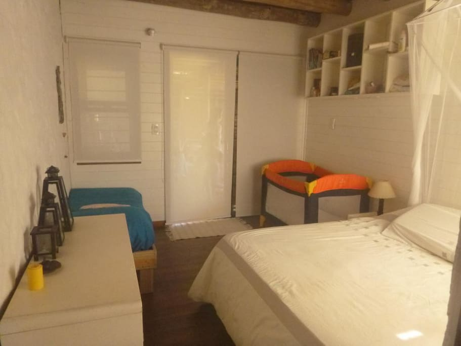 Cama matrimonial y cama simple en dormitorio en suite