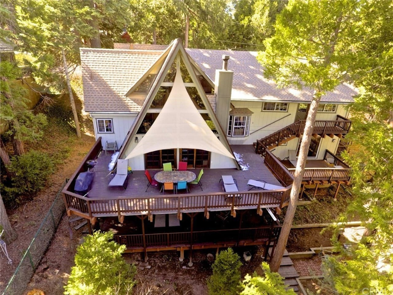 An aerial view of the home showing it's size, the large lovely decks and the beauty of it's forested surroundings. All 5 bedrooms - indeed almost every room - has french doors or sliding doors out to a deck or patio area. Enjoy the feel of privacy!