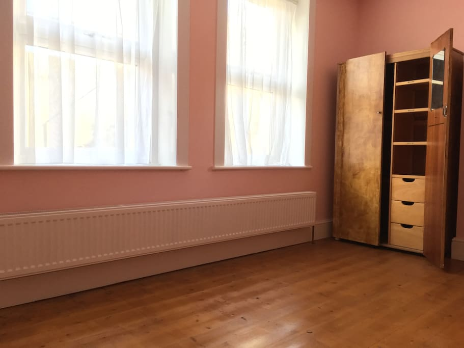 Bedroom 1 available, front-facing, finished wood floor.