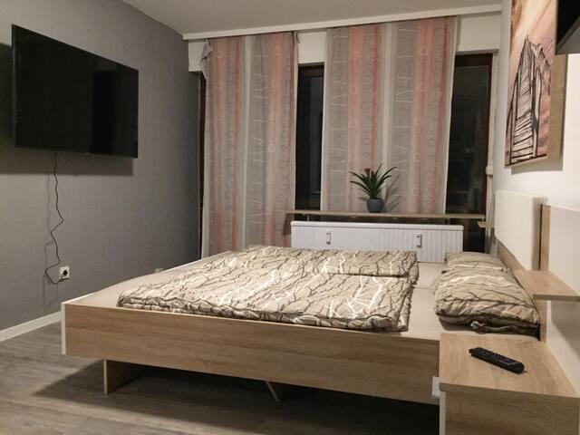 Bett und TV mit Blick auf Balkontür