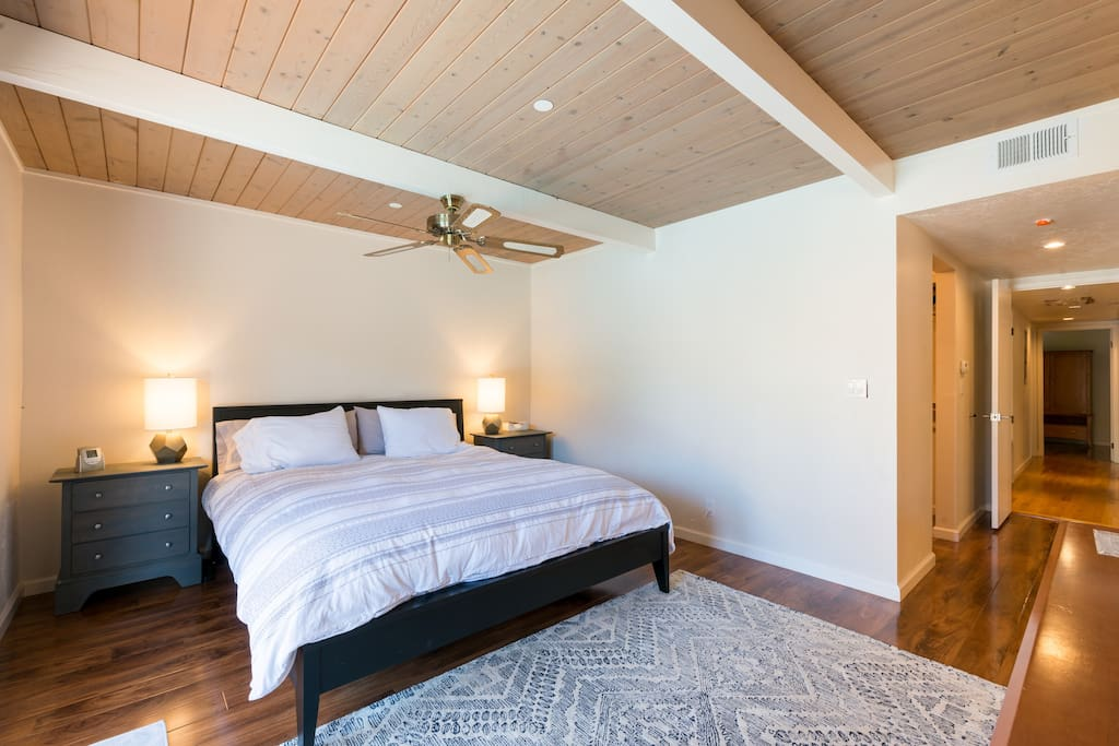 master bedroom w/ cal king bed and french doors to backyard