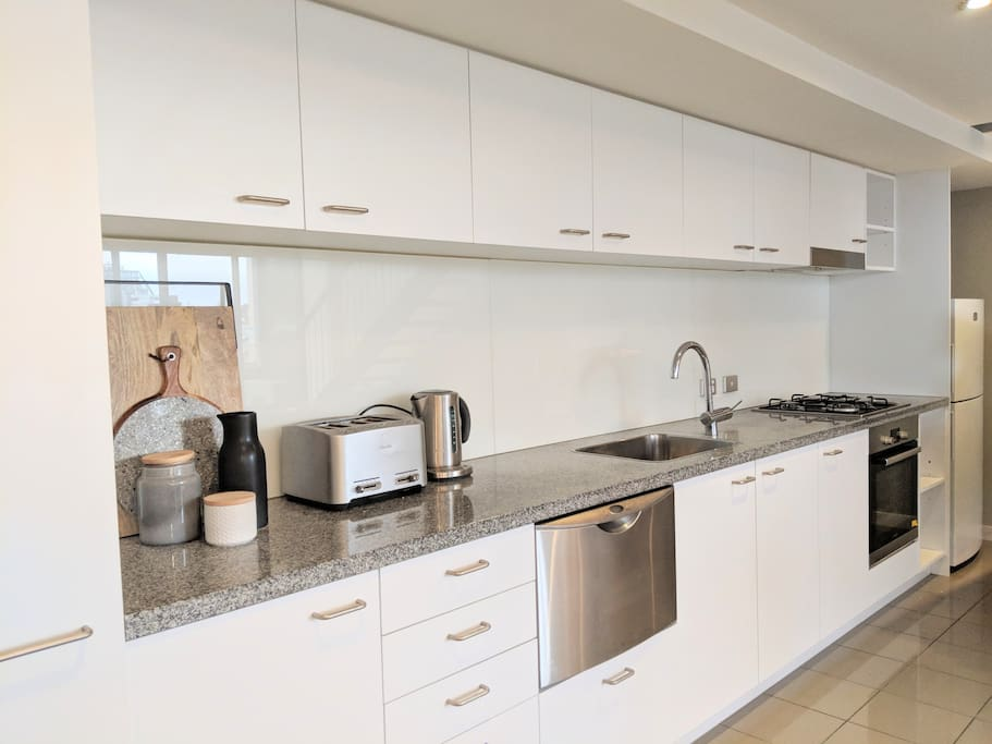 Fully equipped kitchen with 4 slice toaster, kettle, coffee machine, microwave, oven, cooktop, dishwasher and fridge.