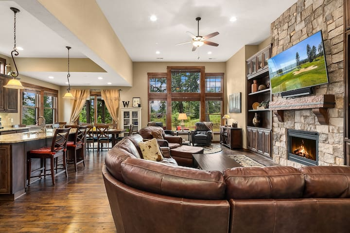 Large great room with a leather furniture and a ledgestone gas fireplace.