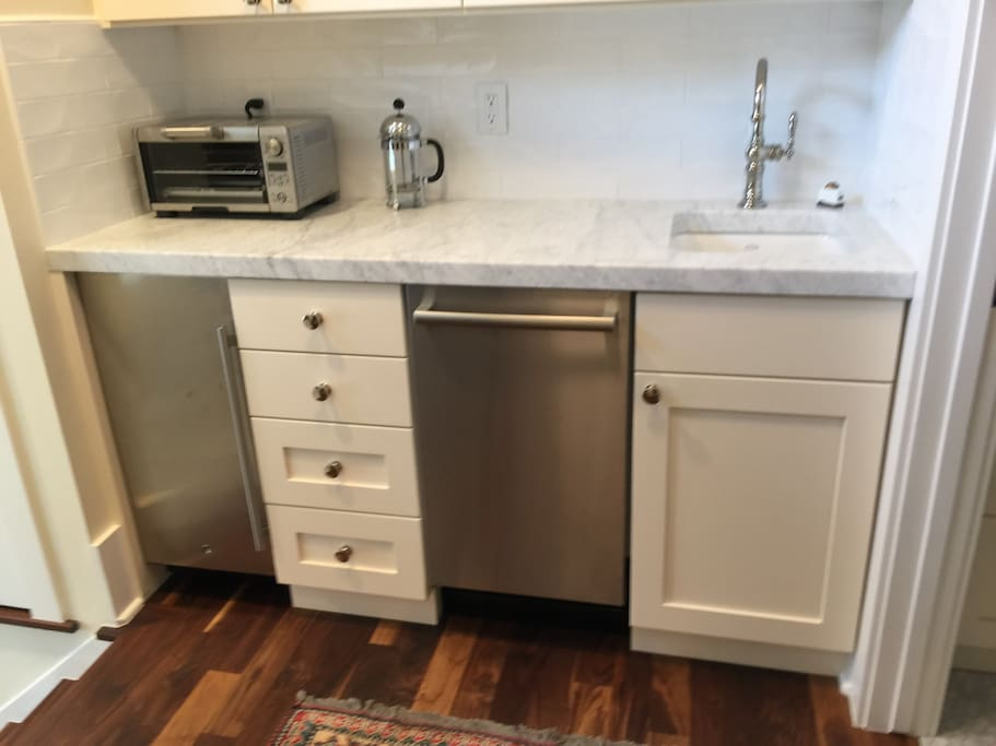 Small Kitchenette with marble counters, dishwasher and refrigerator.