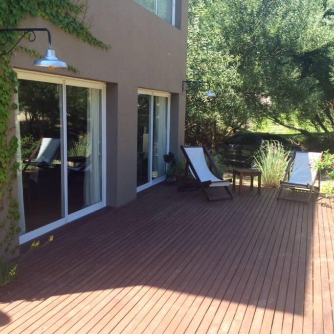 Amplio deck con reposeras y sillas de jardin.