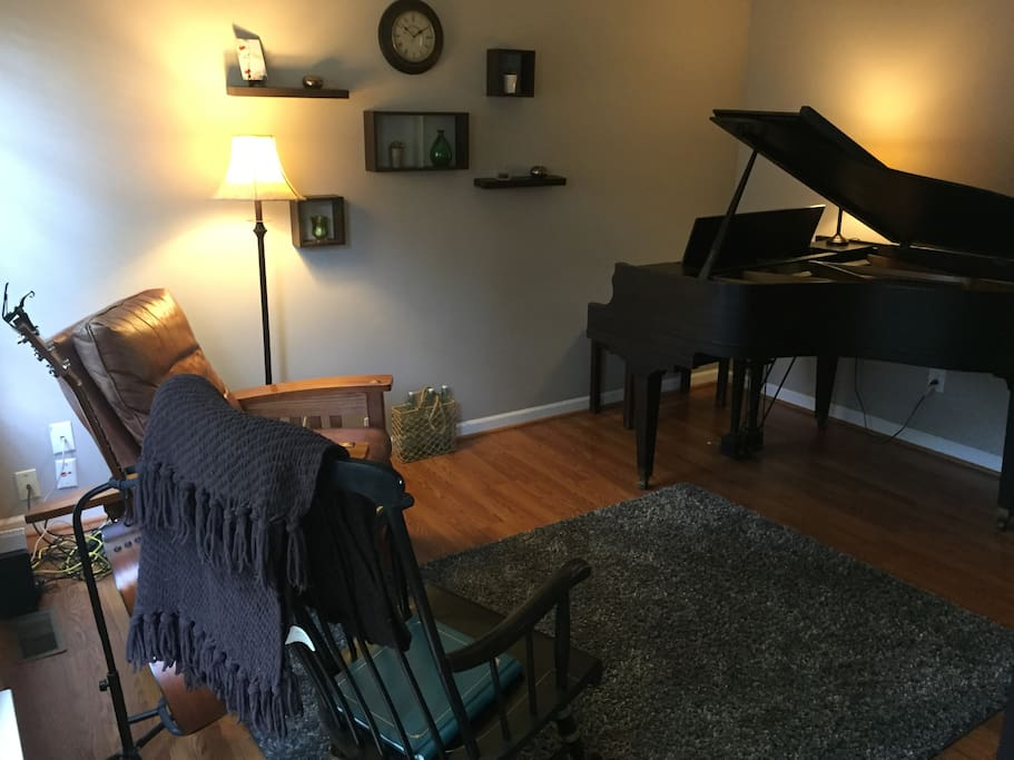 Den with baby grand piano.