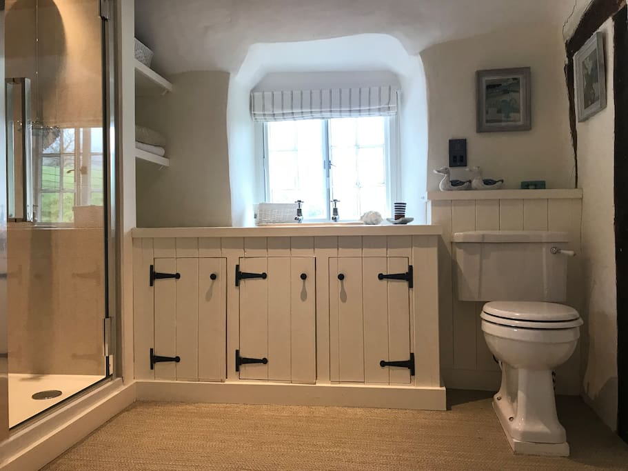 Huge bathroom with cupboards, bath and separate shower