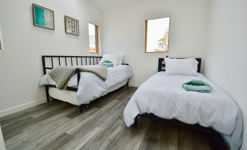 The Twin room is located upstairs and has 3 total beds, with a trundle rolling out from the bed pictured on the left (Note: when all beds are used, this is a tight squeeze! Intended for children and may not be ideal for adults).